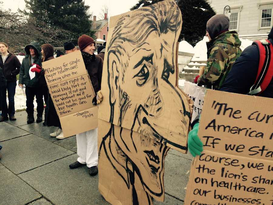 Protestor holds hand-drawn signs depicting the governor.