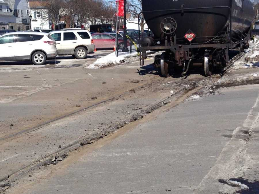 Gas cars have been removed from the crossing, revealing damage to pavement from derailment.