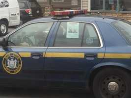 A New York State Police vehicle displays the wanted poster of the two escaped prison suspects on the back passenger window of a police cruiser.