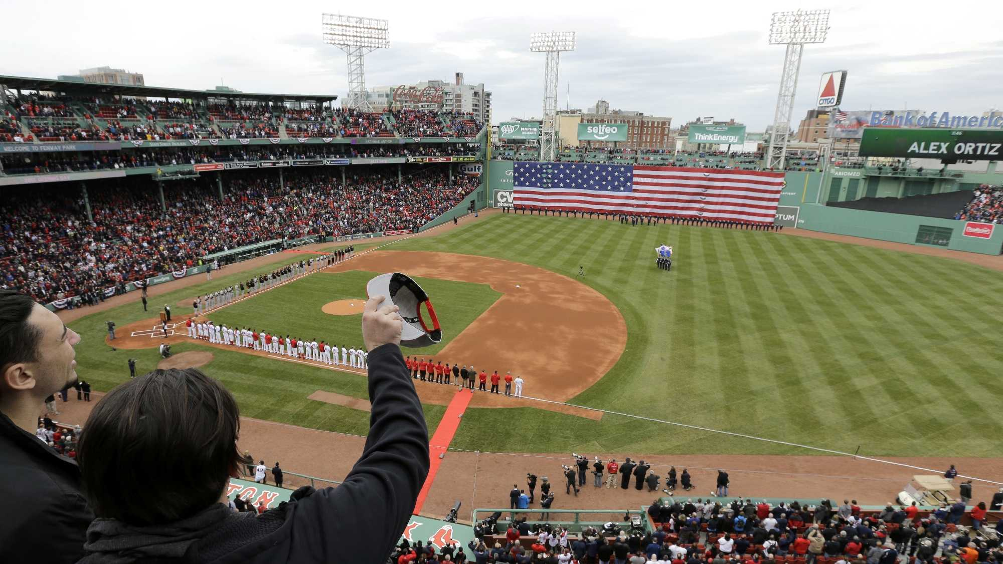 Fans cheer and wave at the conclusion of the singing of the national anthem before the home opener baseball game between the Boston Red Sox and the Baltimore Orioles at Fenway Park, Monday, April 11, 2016, in Boston.