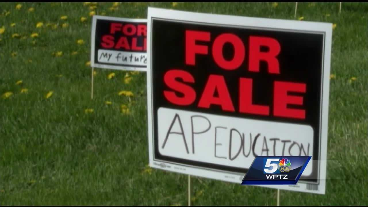 """Burlington High School students scatter """"for sale"""" signs on school lawn representing dissatisfaction with budget cuts."""