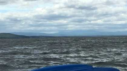 Coast Guard rescuers helped save three people in the water after their vessel overturned Wednesday on Lake Champlain, Vermont.