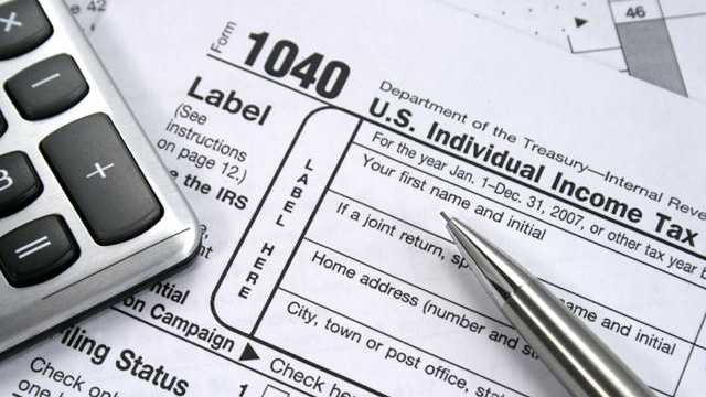 tax forms with pen, calculator, taxes
