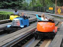 Electric cars run quickly through a trough-like wooden track that twists and turns.