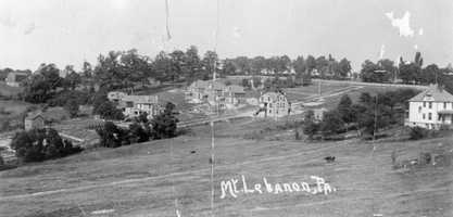 The white house at the far right of this early 1900s postcard is now Rollier's Hardware. The line of trees at the top screens Mt. Lebanon Cemetery from view. A cow stands in the field.
