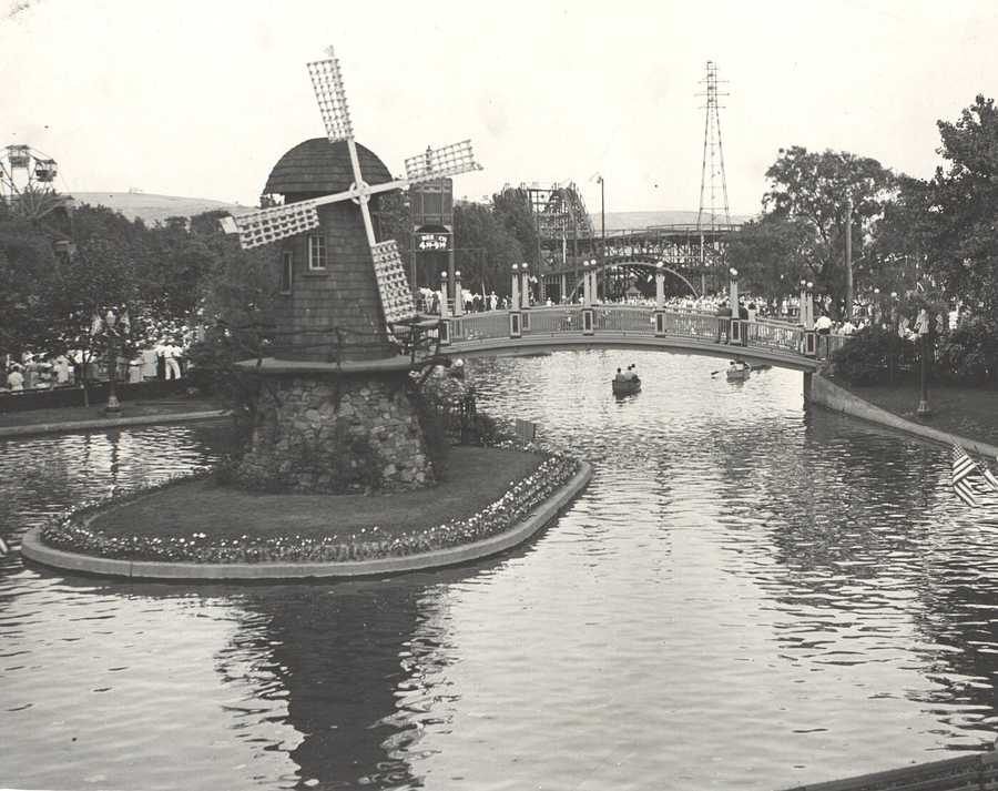 A wide shot of the windmill, the lagoon and the crowds of people surrounding the roller coasters around the park.