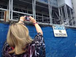 "Fans took photos over a fence with a ""No Trespassing"" sign where the Joe Paterno statue once stood."