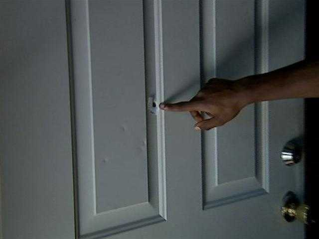 The victim's brother points to the bullet hole in the door.