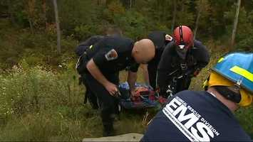 ... while another team went down and strapped the man to a board and helped guide him up the hill.