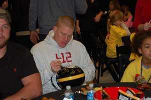 Drew Butler signs the team helmet