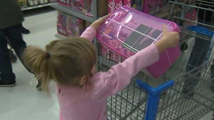 "A girl gets a holiday toy from the ""Shop with a Cop"" program."