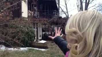 Channel 4 Action News reporter Ashlie Hardway points to the fire damage on 10th Street in Irwin.