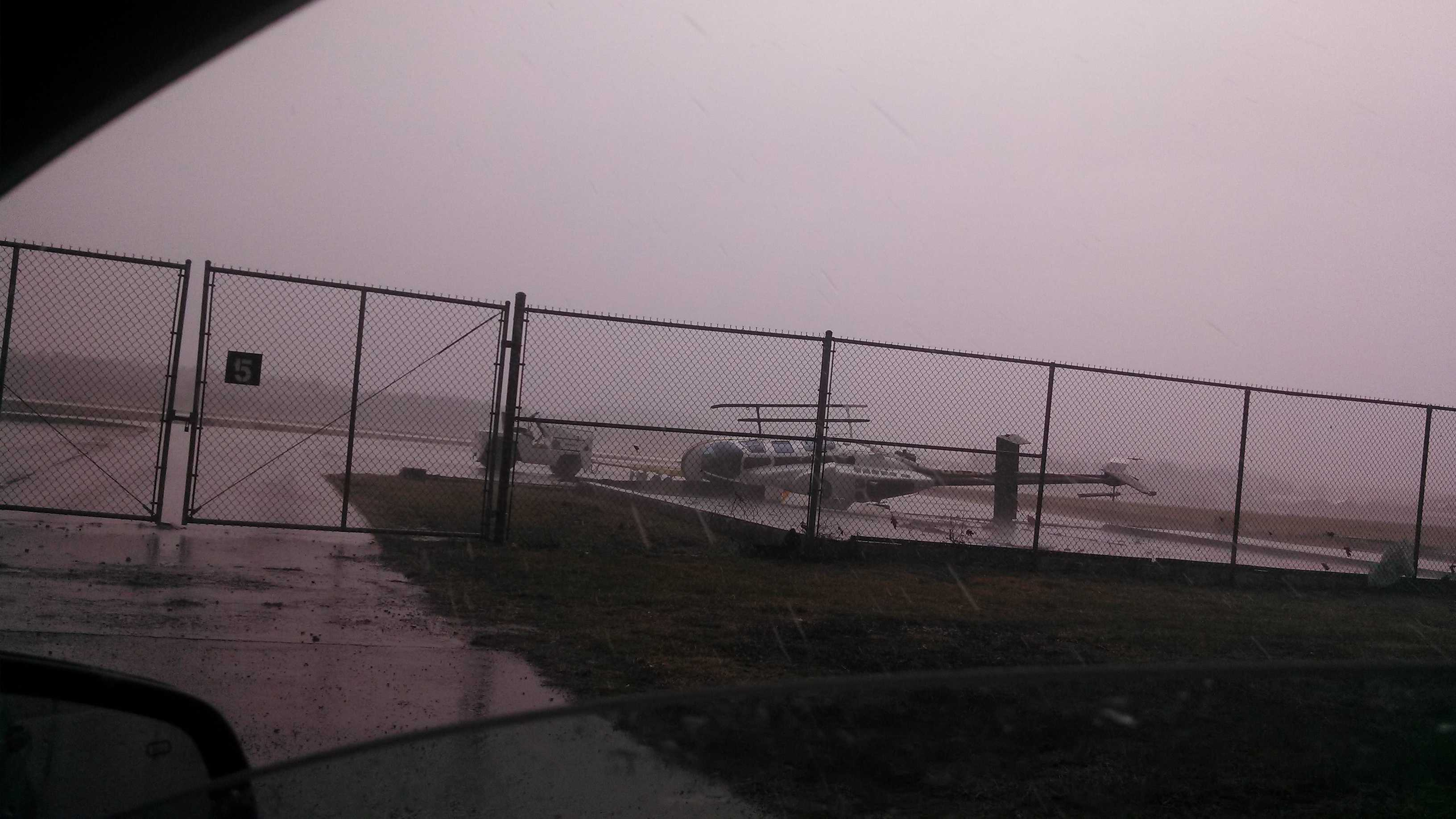 A strong wind blew a Pennsylvania State Police helicopter onto its side at Arnold Palmer Regional Airport during heavy rainfall.