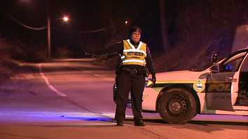 A Pittsburgh police officer directs traffic around the crash scene on Mifflin Road in Lincoln Place.