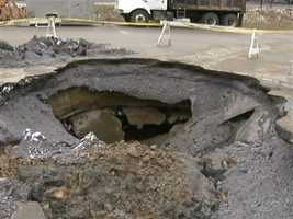 A large hole continues to grow after swallowing several parking spaces in the lot outside Dormont Pool.