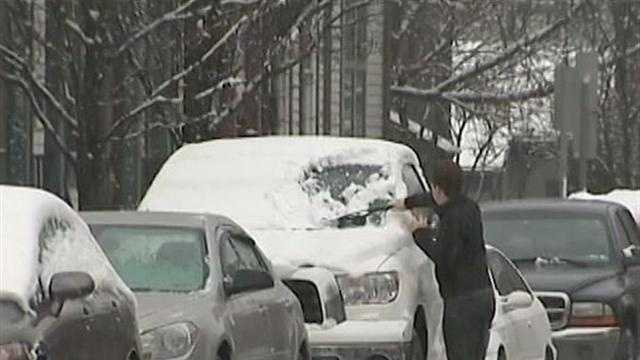 A man brushes snow off his vehicle's windshield.