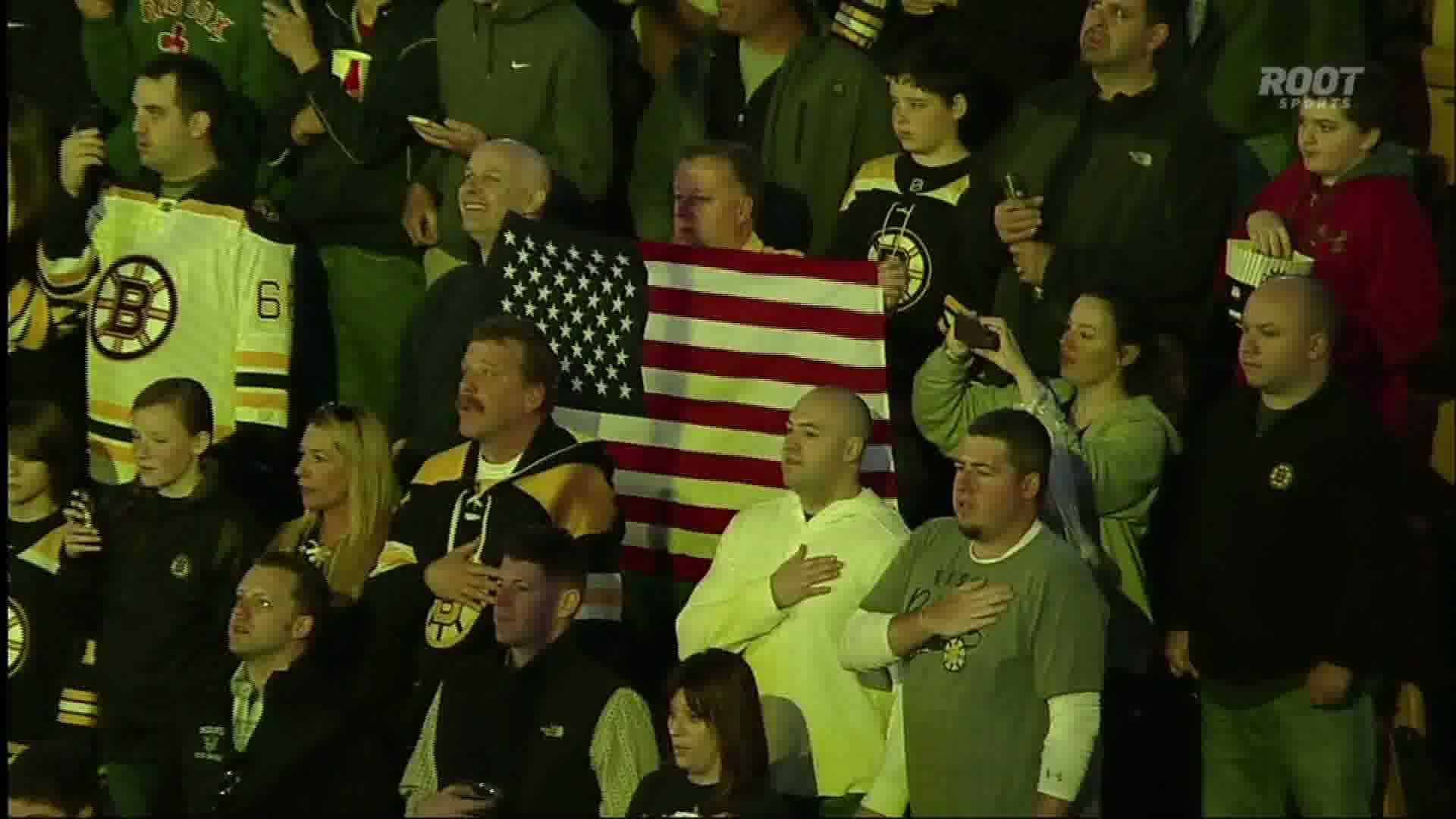 Boston Bruins fans sing the national anthem before a game against the Penguins. The game was postponed while police searched for a Boston Marathon bombing suspect.