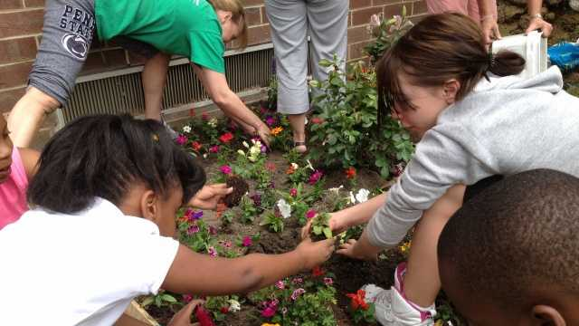 Clairton Elementary students plant a garden in honor of Connor Zink outside the school.