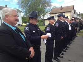A police officer dons his white gloves for the funeral Mass.