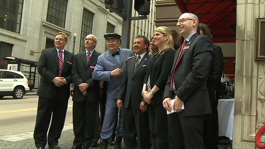 "Mr. McFeely of ""Mister Rogers' Neighborhood"" poses with Macy's officials under the Kaufmann's clock."