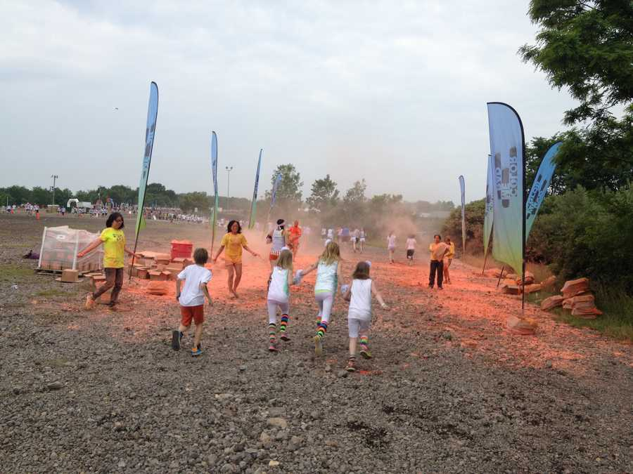 Volunteers stand on the side of the course and throw packs of colored cornstarch at the runners at different intervals.