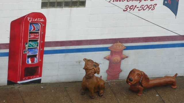 For about eight years, two concrete dog statues weighing hundreds of pounds have greeted residents and customers outside Forbes Auto Body in uptown Pittsburgh. Now, one of those statues -- a giant wiener dog -- is missing.