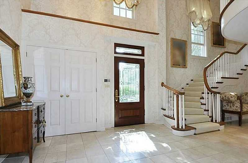 The foyer features multiple windows and a grand winding staircase.
