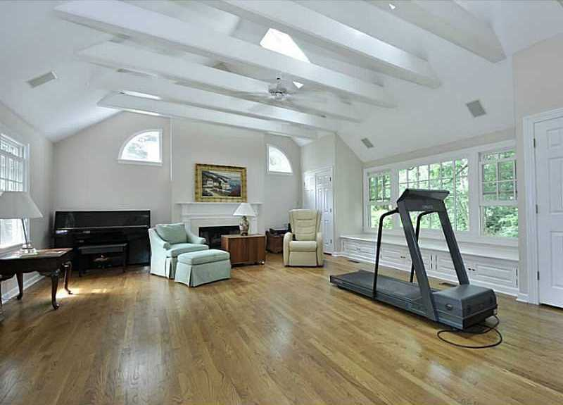 The den space not only has beautiful vaulted ceilings, but also can serve a variety of purposes. It currently features a piano and treadmill.