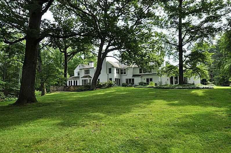 The sprawling lawn includes perfectly placed trees, providing the home with shade and privacy.