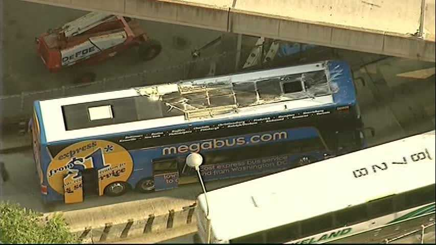 Authorities are investigating how a double-decker bus from Pittsburgh to New York got wedged on a ramp at the Port Authority bus terminal in Manhattan.