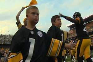 Steelers take the field with some cheering fans leading them on