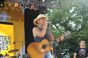"Kenny Chesney wears a T-shirt that benefits his ""Spread the Love Fund"" in support of Boston Marathon bombing victims during the GMA Summer Concert Series in Central Park, on GOOD MORNING AMERICA, 8/9/13,"