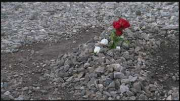 Friends placed a flower in the gravel along the train tracks near the spot where Trevor Fluharty was struck.