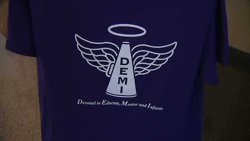 """The name Demi now stands for """"Devoted to Educate, Mentor and Inform."""" Gateway cheerleaders will wear this purple T-shirt at tonight's football game."""