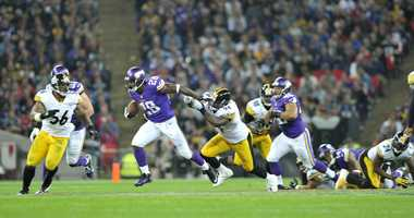 Vikings running back Adrian Peterson fights for yardage.