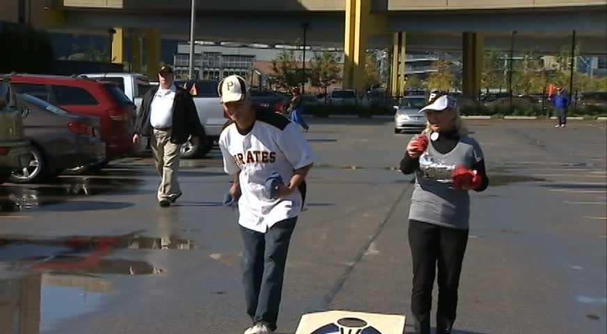"""A game of """"cornhole"""" in the parking lot."""