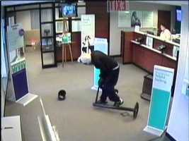 """Police said the robber fled the bank and got into the driver's seat of a red SUV parked nearby. Witnesses said he had trouble starting the vehicle and two passengers were heard telling him to """"hurry up,"""" according to police. He eventually got the vehicle started and nearly struck a police car that was en route to the bank, police said."""