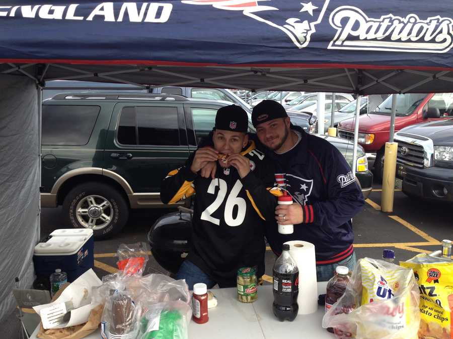 A Steelers fan and a Patriots fan enjoy some tailgating food before the game at Gillette Stadium.