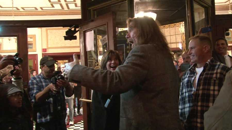 """""""Hacksaw"""" Jim Duggan leads the crowd in a chant of """"U-S-A"""" outside the theatre."""