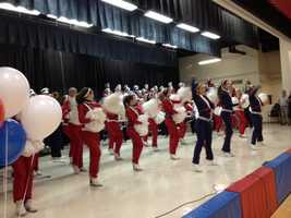 """The high school band played as Autumn's classmates held """"welcome home"""" signs for her dad. The big surprise was orchestrated by her teachers and administrators."""