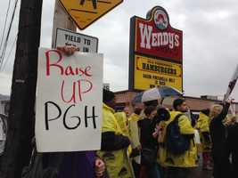 Fast-food workers and labor organizers are marching, waving signs and chanting outside restaurants on Pittsburgh's North Side.