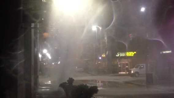 Water shoots into the air at the corner of Fourth and Wood streets.