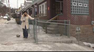 Amber Nicotra holds onto a fence to keep her balance on the icy sidewalk on Woodlawn Avenue in Wilkinsburg.