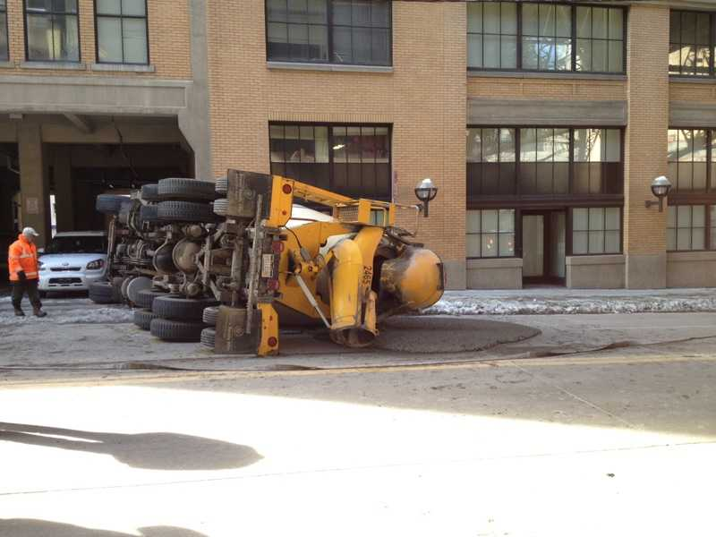 The truck landed on its side and spilled cement on Second Avenue.