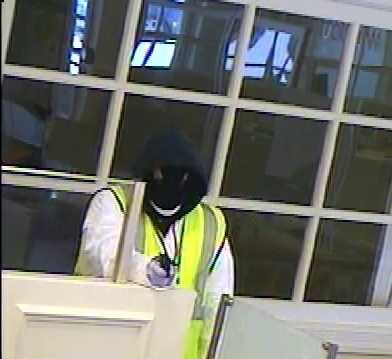 Both robbers wore black ski masks and white plastic coveralls. Robber #1 is described as a white man, about 5 feet 9 inches tall, thin to medium build, with a neon yellow reflective vest and dark shoes. He showed a dark-colored handgun.