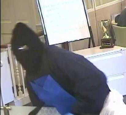 Both robbers wore black ski masks and white plastic coveralls. Robber #2 was described as male, medium build, around 5 feet 10 inches, wearing blue jeans under white plastic coveralls pants, a dark navy jacket, and carrying a nylon reusable shopping bag.