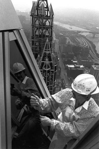 A worker installs glass on a spire at the top of One PPG Place. The steel skeleton of a spire is in the background, with a 40-plus-story view of the Mon Valley as it looked just over 30 years ago.