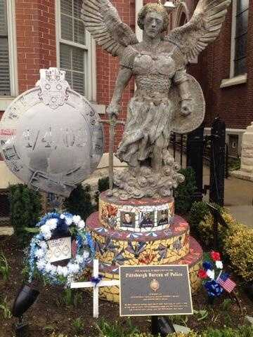 Flowers mark a solemn fifth anniversary at the Fallen Officers Memorial in Bloomfield