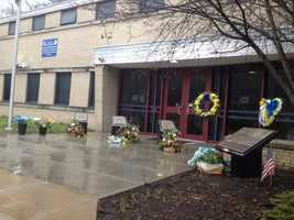 Flowers are left at a memorial for Officers Paul Sciullo, Eric Kelly and Stephen Mayhle at the Zone 5 police station