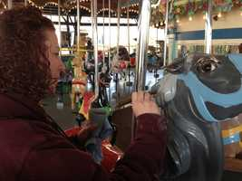 A worker paints one of the horses on the carousel